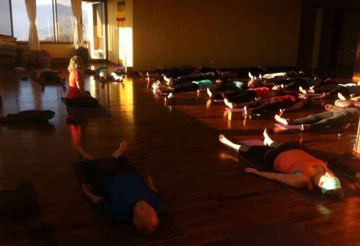IRest yoga Nidra meditation session. People made themselves comfortable on yoga mats and with blankets and bolsters.