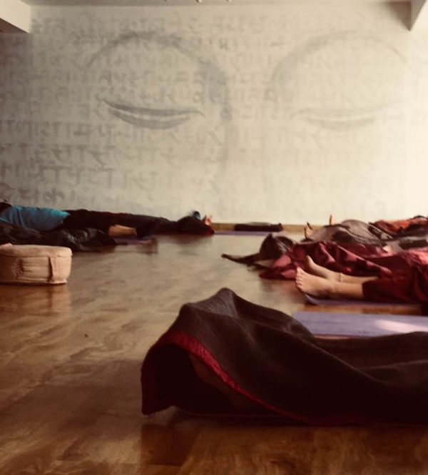 Students have settled in for an IRest yoga Nidra meditation. IRest combines modern psychology and neuroscience science with ancient yogic and Buddhist wisdom, hence the Buddha eyes on the mural.